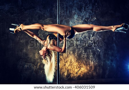 Young blond sexy pole dance woman on old wall background. Contrast colors effect.