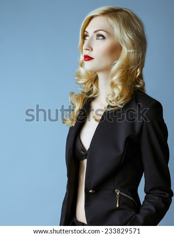 Young blond sexy woman in a business suit on a grey background. Perfect skin and make up. Sexy red lips. Studio shot - stock photo