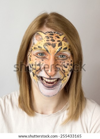 Young blond slav girl with face painting jaguar