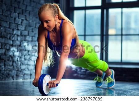 Young blond slim woman do abdominal exercises with wheel in modern interior on window background. - stock photo
