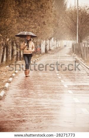 Young blond urban woman walking under rain - stock photo