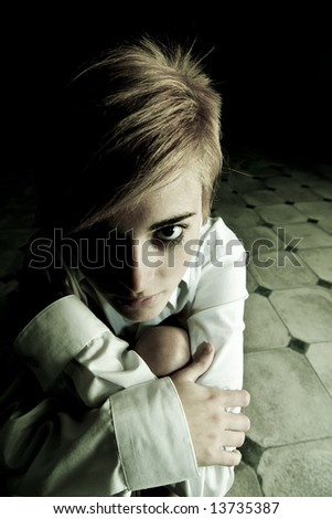 Young blond woman alone in the darkness - stock photo