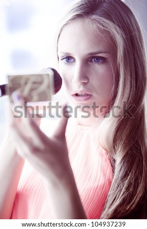 young blond  woman apply blush by the window natural light, small amount of grain added - stock photo