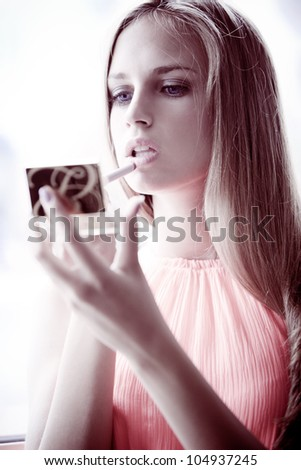 young blond  woman apply lipstick by the window natural light, small amount of grain added - stock photo