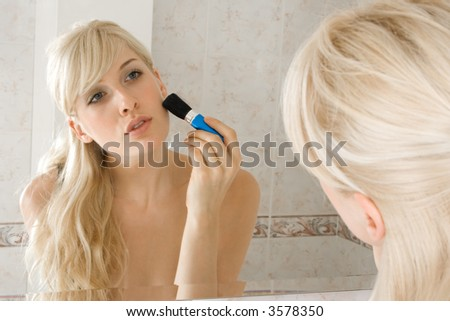 young blond woman applying make up in front of mirror in bathroom - stock photo