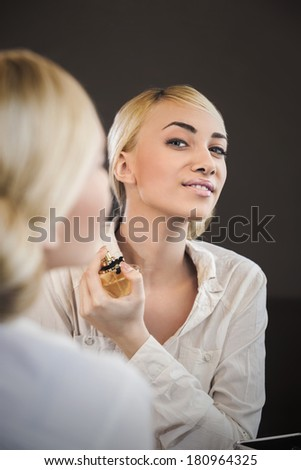 Young blond woman applying perfume looking at mirror - stock photo