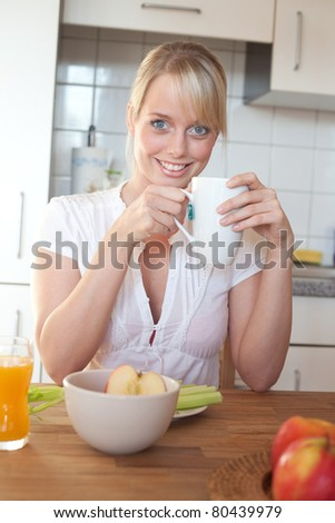 young blond woman at a table with breakfast/young blond woman with breakfast at a table in her kitchen