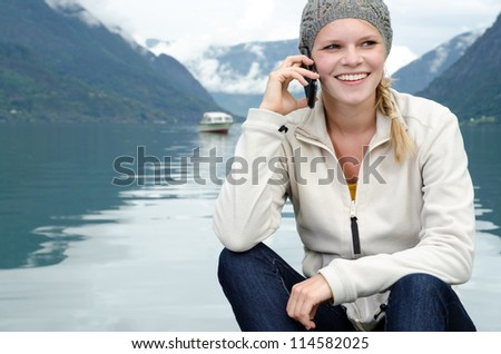 young blond woman called up with her Smartphone with a fjord in Norway in the background - stock photo