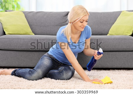 Young blond woman cleaning a carpet in front of a gray sofa with a rag at home - stock photo