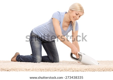 Young  blond woman cleaning a carpet with a handheld vacuum cleaner isolated on white background - stock photo