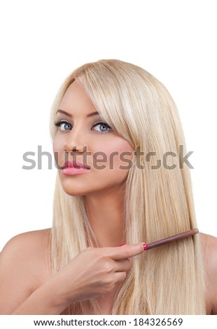 Young blond woman combing her hair - stock photo
