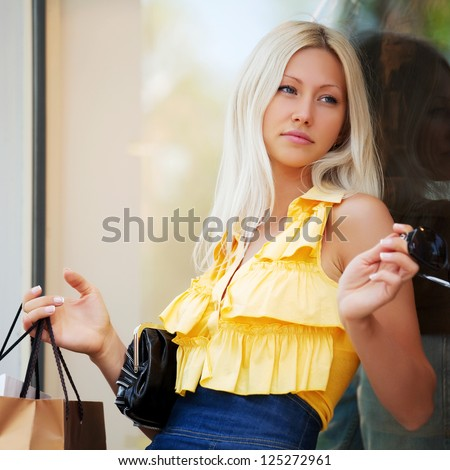 Young blond woman daydreaming against a shop window - stock photo
