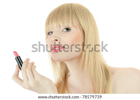 Young blond woman doing makeup with lipstick - stock photo