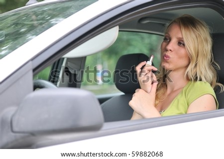 Young blond woman doing makeup with lipstick in car
