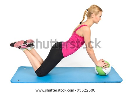 Young blond woman doing pushups on medicine ball - stock photo