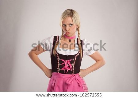 young blond woman dressed with dirndl for oktoberfest is disappointed