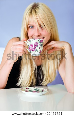 young blond woman drinks tea - stock photo