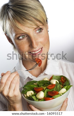 young blond woman eating fresh salad close up - stock photo