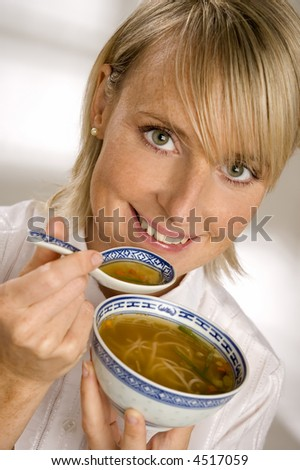 young blond woman eating noodle soup close up - stock photo