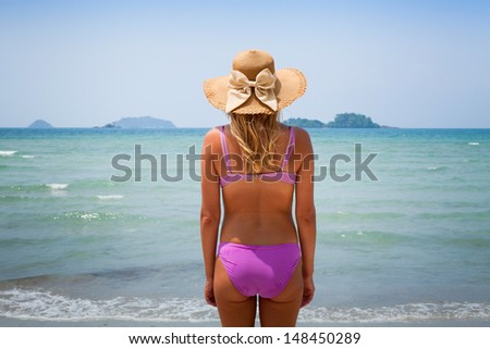 young blond woman enjoying the beach, back - stock photo