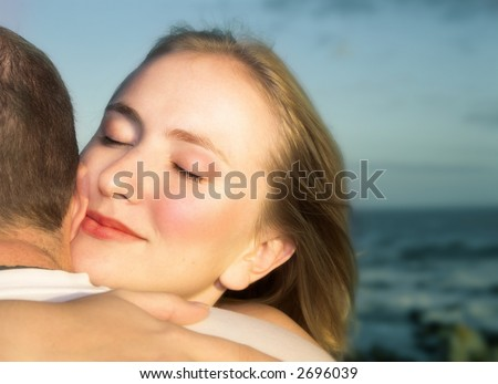 young blond woman giving her partner a hug with loving expression on face against blue sky and sea - stock photo
