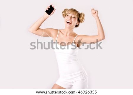 young blond woman hears music with a mp3 player and dances