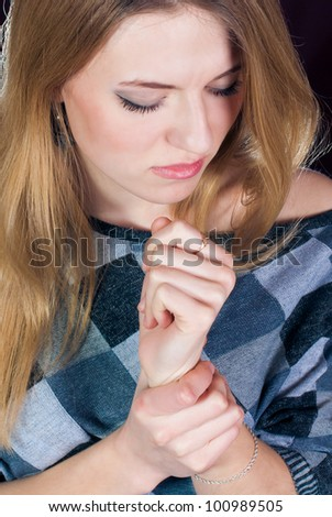 Young blond woman holding her wrist in pain - stock photo