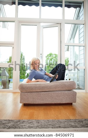 Young blond woman holding tablet-pc while lying on couch - stock photo