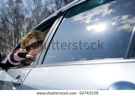 young blond woman in a blue car in sun-glasses. on glass of the car reflection blue sky and sun - stock photo