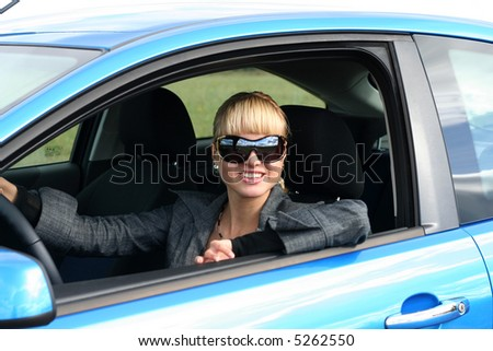 young blond woman in a blue car in sun-glasses. She is smiling - stock photo