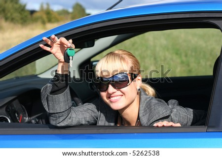 young blond woman in a blue car with key from it - stock photo