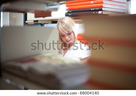 young blond woman in a library with a big book/blond woman with a big book