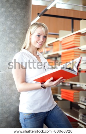 young blond woman in a library with a book/blond woman in a library - stock photo