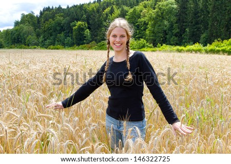 Young blond woman in a wheat field - stock photo