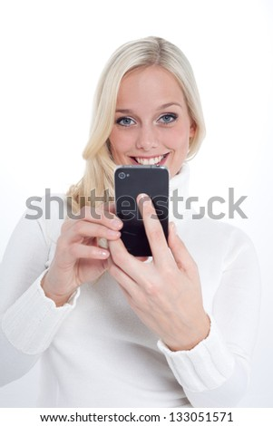 young blond woman in a white pullover with her smartphone/blond woman with a smartphone/woman with her smartphone