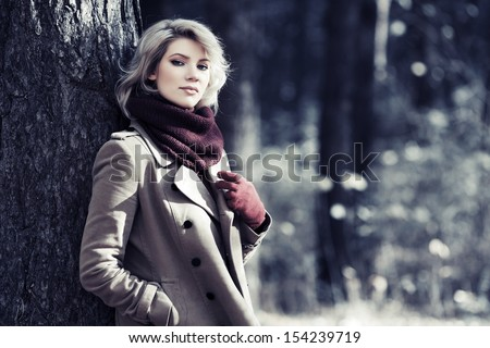 Young blond woman in autumn forest - stock photo