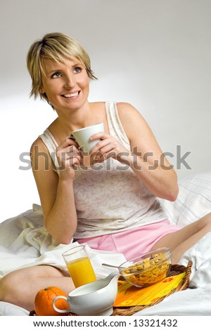 young blond woman in bed for breakfast - stock photo