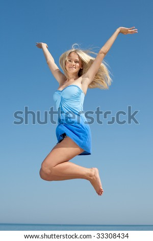 Young blond woman in blue jumping on background of the sky