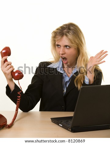 Young blond woman in business suit sitting at a desk with an angry expression on her face while holding the receiver of a phone away from her ear - stock photo