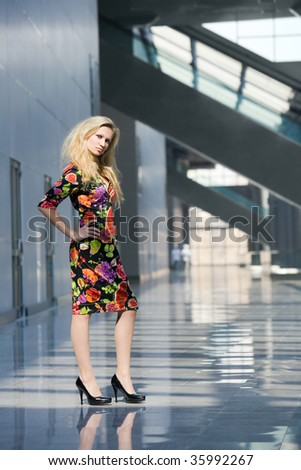 young blond woman in colorful dress standing in hall