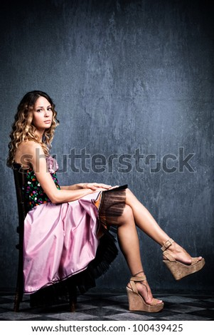 young  blond woman in elegant pink dress sit on chair in empty grunge room with tiled floor - stock photo