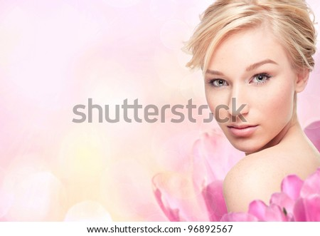 Young blond woman in flower on pink background