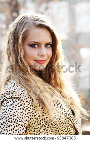 young blond woman in leopard jacket - stock photo