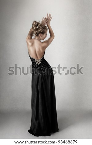 Young blond woman in open-back black elegant dress - stock photo