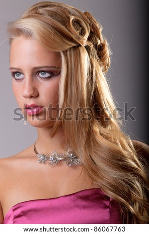 Young blond woman in pink dress and pink lipstick. Fashion studio portrait. - stock photo