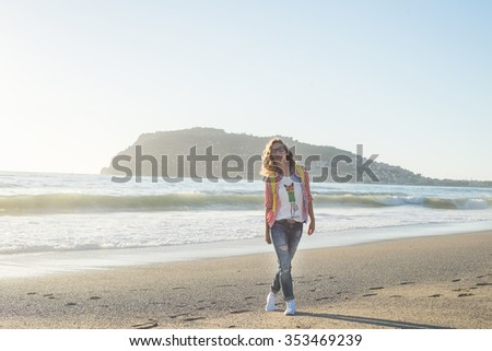 Young blond woman in red checkered shirt, jeans and white sneakers walking along beach and the stormy ocean on sunny winter day