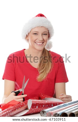 Young blond woman in santa hat packing christmass gift - stock photo