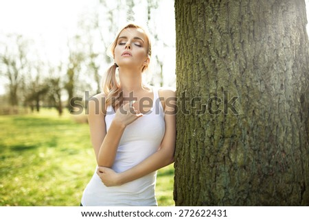 Young blond woman in the fragrant orchard - stock photo
