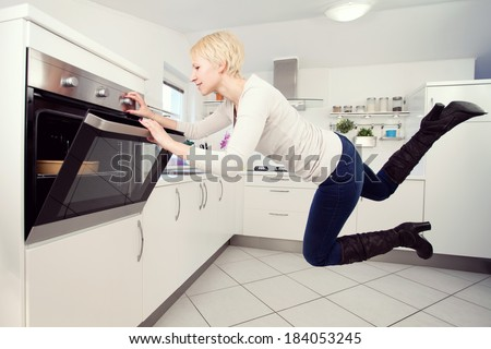 Young blond woman in the kitchen levitating - stock photo