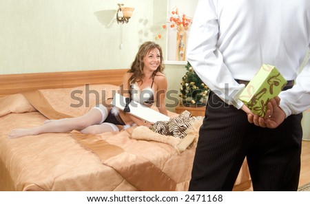 young blond woman in white fur coat and black bikini making a mobile call and a man holding white gift box in his hands, both sitting on the bed in nice interior - stock photo